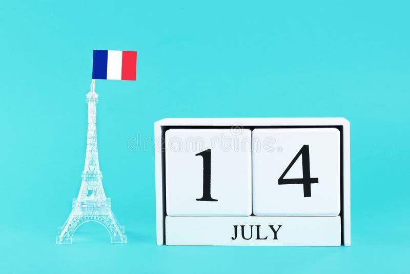 艾菲尔铁塔的缩样有法国旗子和木日历的在蓝色背景 假日的概念是7月14日, 免版税库存图片