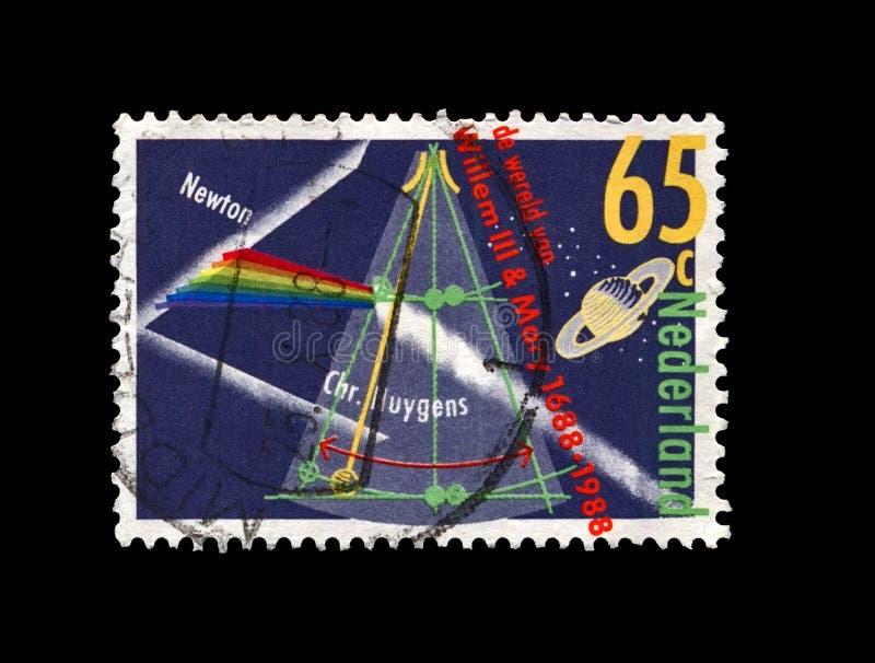 艾萨克・牛顿发现的棱镜分裂的光,行星基督徒观察的土星惠更斯,摆钟,大约1988年 免版税图库摄影