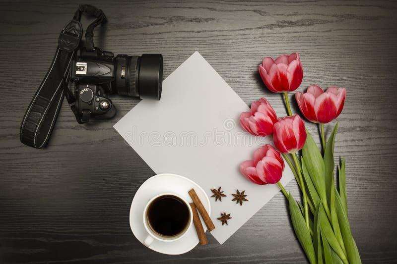 节假日概念 桃红色郁金香、一杯咖啡,dslr照相机和纸片花束在黑木背景的 直接地 免版税库存照片