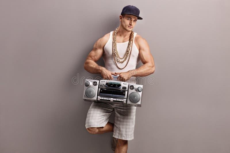 节律唱诵的音乐的年轻人给拿着收音机穿衣 免版税库存图片
