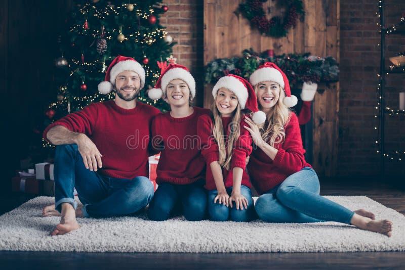 节日快乐 一张爸爸妈妈姐姐哥哥在屋内围着花园树坐在地上,共度夜夜的照片 免版税库存照片