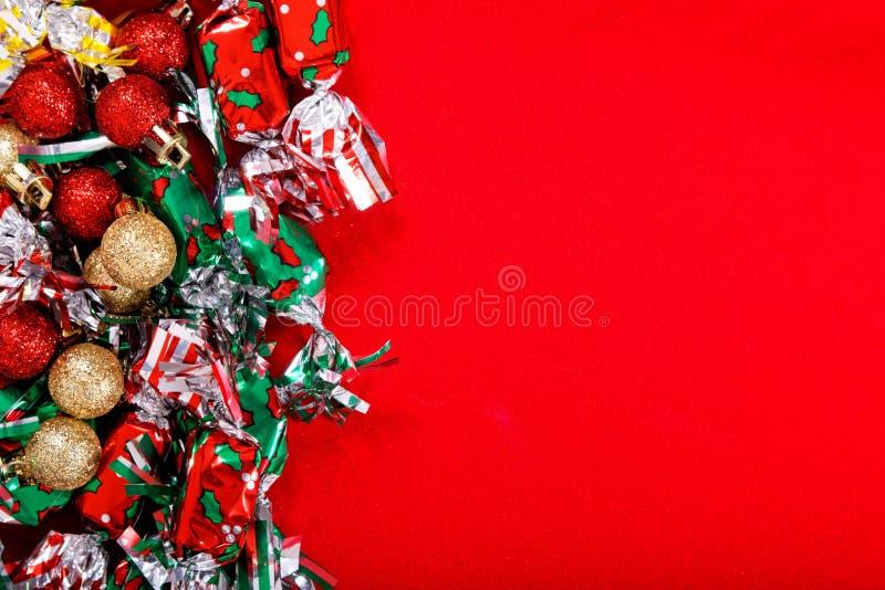 节日晚会、新年、在红色背景的圣诞节或者生日糖果和闪烁的球背景球 库存图片