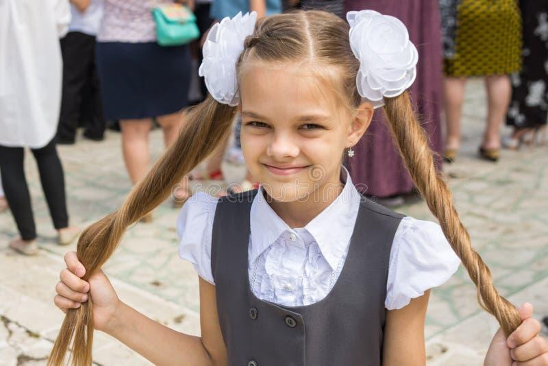 节日的女小学生9月1日在她的手上握她长的头发 库存照片