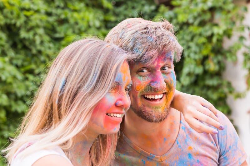 节日holi,人概念-采取在五颜六色的肮脏的衣裳的年轻夫妇selfie 免版税库存照片