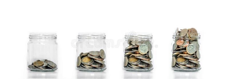 节约金钱,玻璃瓶子安排与在生长的硬币,在白色背景里面 库存图片