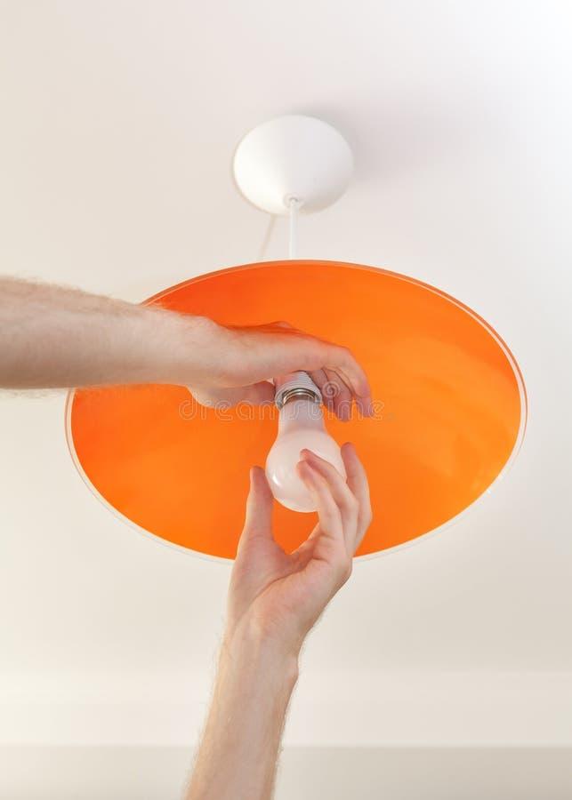 节能LED电灯泡特写镜头在人的手,灯的替换上在天花板发光设备的 免版税图库摄影