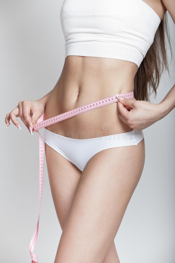 节食。少妇测量的腰部 免版税库存图片