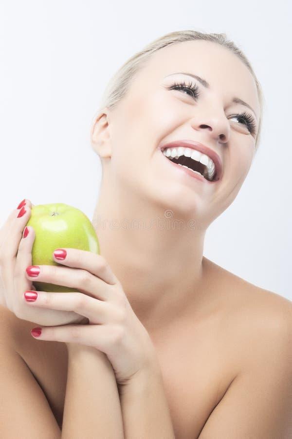 节食与绿色苹果计算机的愉快的微笑的妇女。健康生活方式, 免版税库存图片