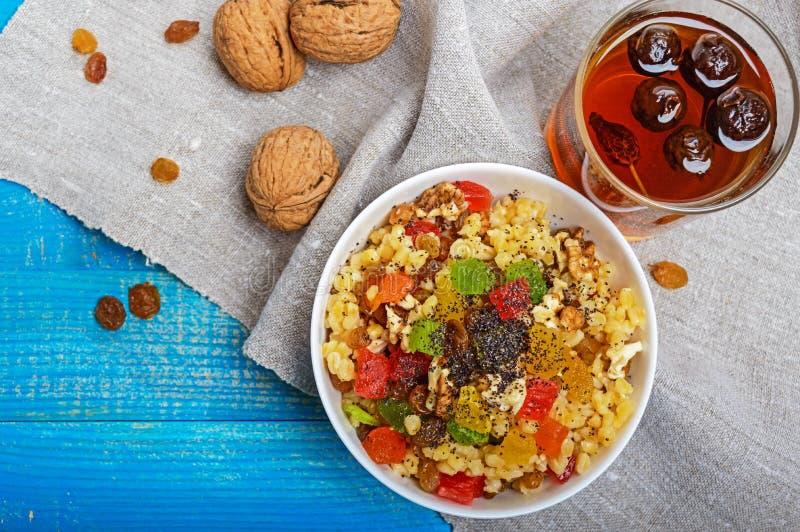 节食健身与坚果,葡萄干,切片的麦子粥柑桔葡萄柚,桔子,猕猴桃,罂粟种子,蜂蜜,在白色 免版税库存图片