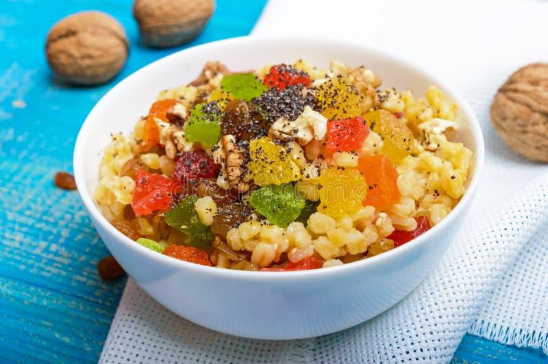 节食健身与坚果,葡萄干,切片的麦子粥柑桔葡萄柚,桔子,猕猴桃,罂粟种子,蜂蜜 免版税图库摄影