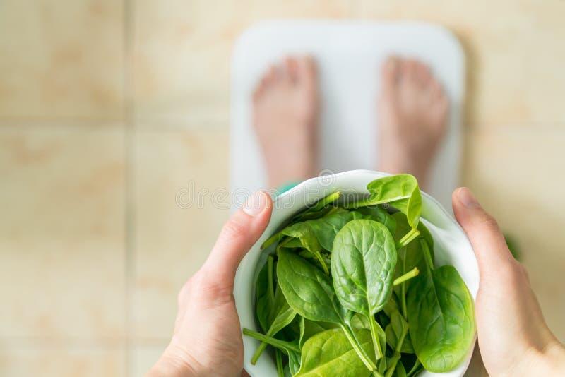 节食和锻炼概念- athlectic衣裳的女性吃蔬菜沙拉的 图库摄影
