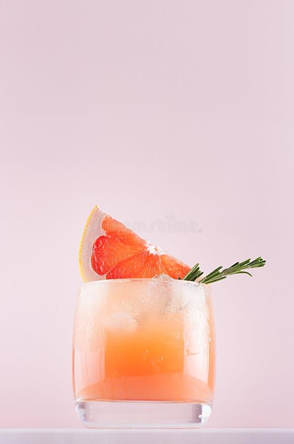 节食的戒毒所水用葡萄柚汁、冰块、绿色迷迭香、被切的柑橘在软的粉红彩笔和白色背景 免版税库存照片