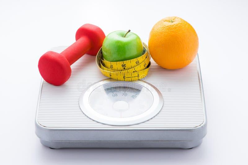 节食的重量损失减肥下来概念 在白色重量等级的特写镜头测量的磁带 免版税库存图片