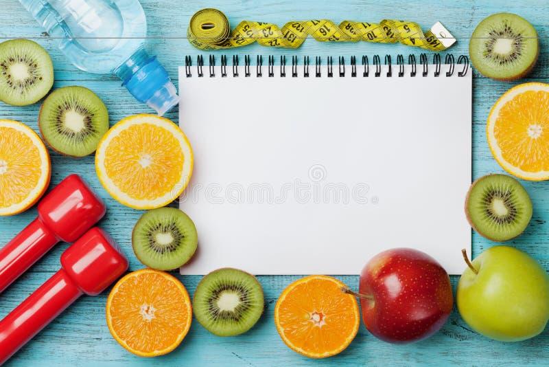节食计划、菜单或者节目、卷尺、水、哑铃和新鲜水果饮食食物在蓝色背景,戒毒所概念的 库存图片