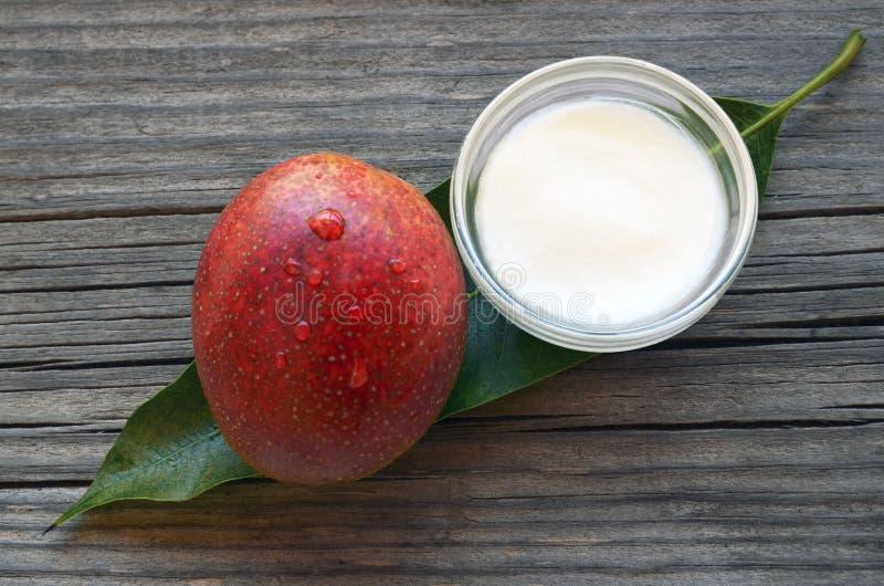 芒果在一片玻璃碗的身体黄油和新鲜的成熟有机芒果果子和叶子在老木背景 图库摄影