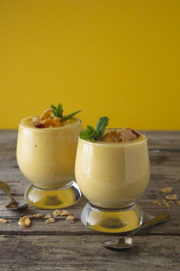 芒果奶昔或圆滑的人在一块玻璃在老木背景 芒果奶昔 夏天刷新的饮料概念 免版税库存图片