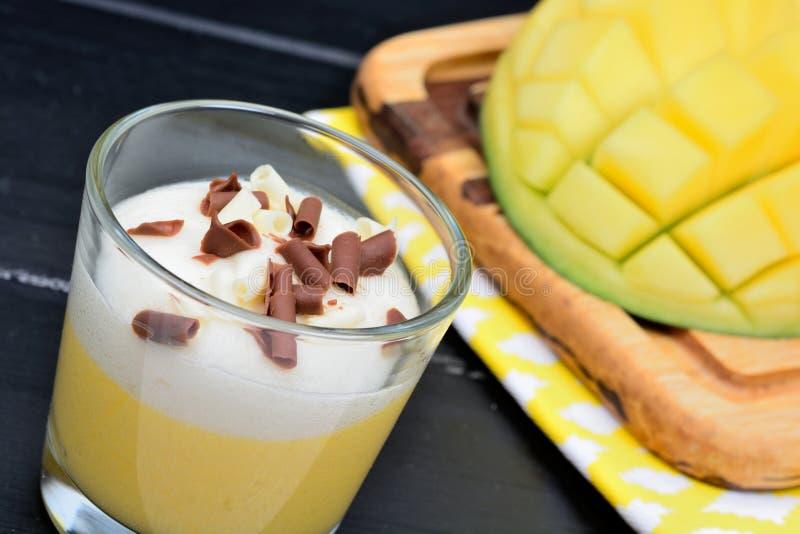 芒果果子奶油甜点与被鞭打的奶油和巧克力的在木桌上的一个玻璃瓶子 免版税库存图片