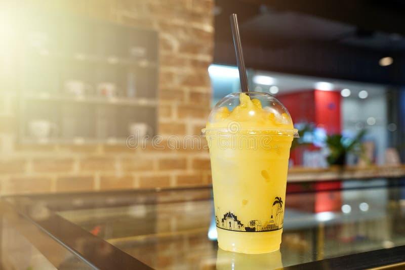芒果水果的frappe、圆滑的人和震动在塑料在饮料商店拿走杯子在木桌上 库存照片