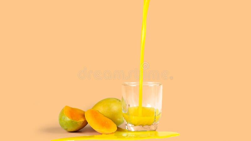 芒果汁,在橙色背景 库存图片