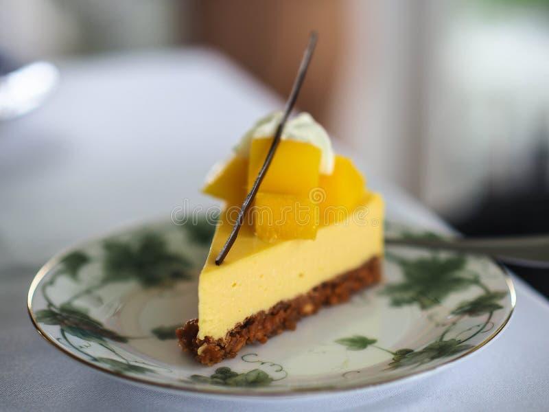 芒果cheesepie冠上用新鲜的芒果在葡萄酒板材服务 库存照片