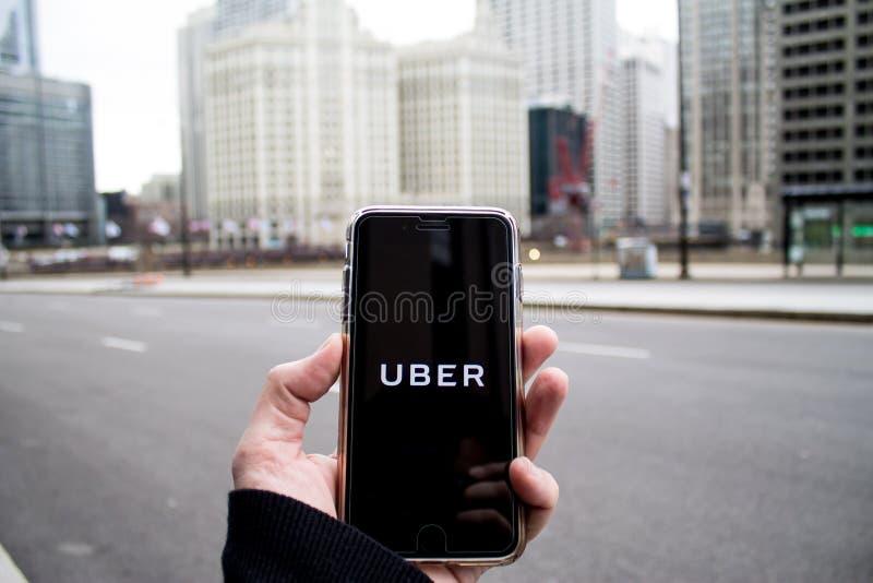 芝加哥, IL,美国, 2月21,2017,拿着有开放Uber的app的人一个智能手机在城市为仅社论使用 库存图片