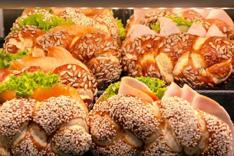 芝麻与三文鱼和火腿装填的小圆面包三明治在显示 免版税库存图片