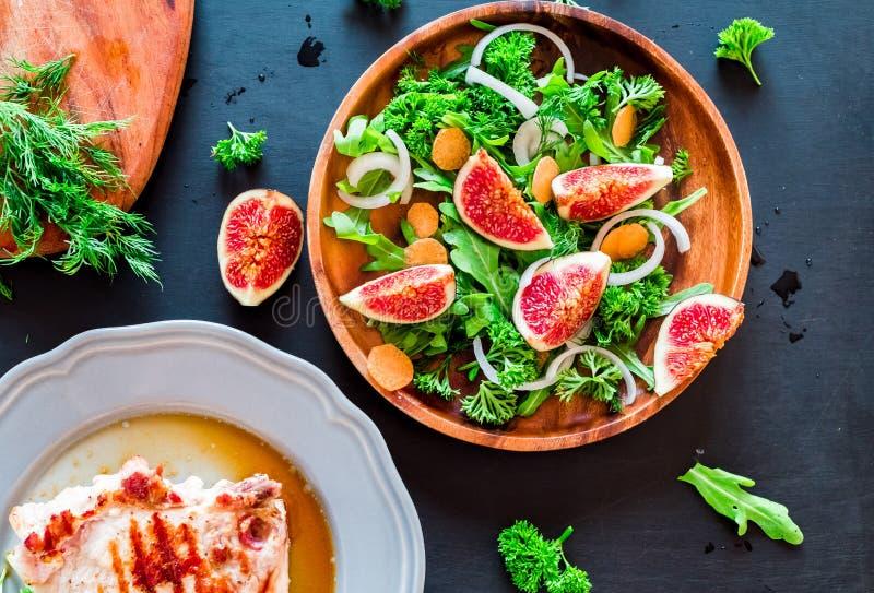 芝麻菜,在一块棕色陶器板材的无花果秋天沙拉在黑暗的背景 顶视图 库存照片