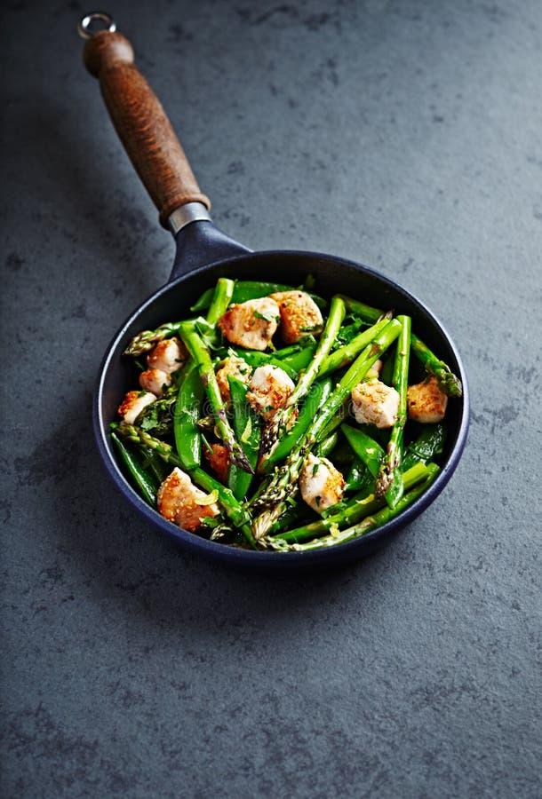 芝麻鸡用绿色芦笋和糖爆豌豆调味与柠檬皮混乱油煎 免版税图库摄影