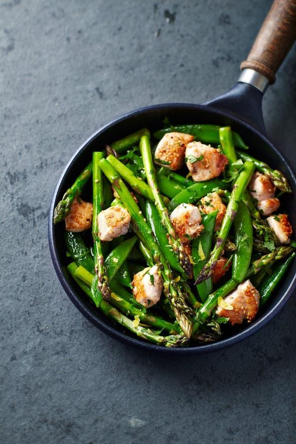 芝麻籽鸡用绿色芦笋和糖爆豌豆 免版税库存图片