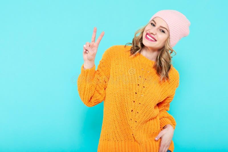 芥末的疯狂的美丽的时髦女孩上色了做和平标志手势的毛线衣和桃红色童帽帽子 冷静妇女年轻人 库存照片
