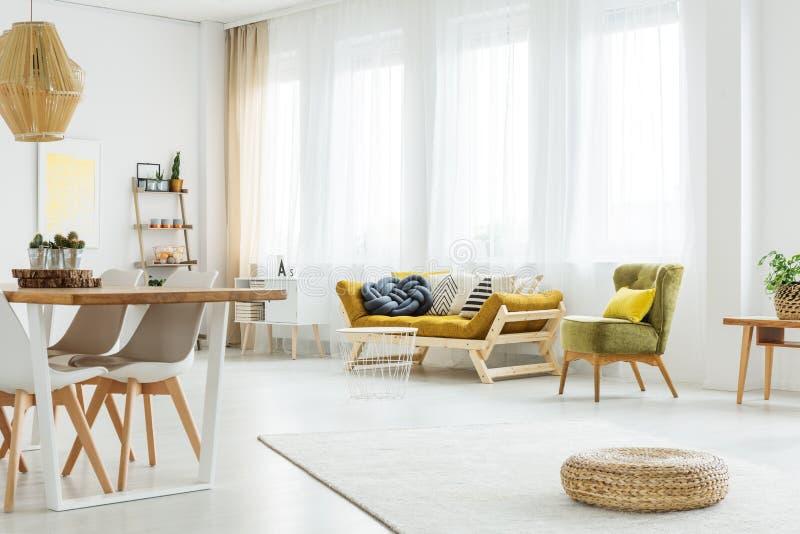 芥末长沙发和绿色椅子 库存照片