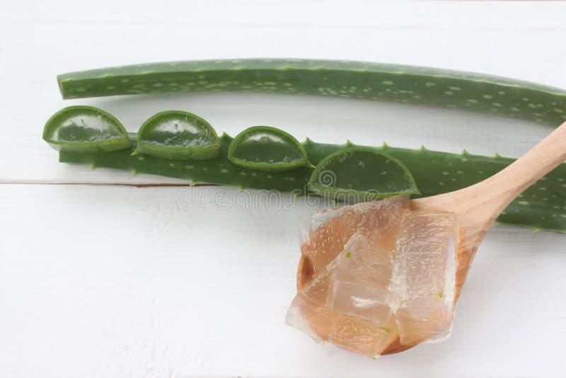 芦荟在一白色木安置的一把木匙子的维拉胶凝体 库存图片