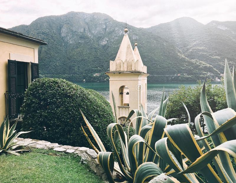 芦荟维拉树、钟楼和一部分的反对绿色山和湖背景的房子  库存图片