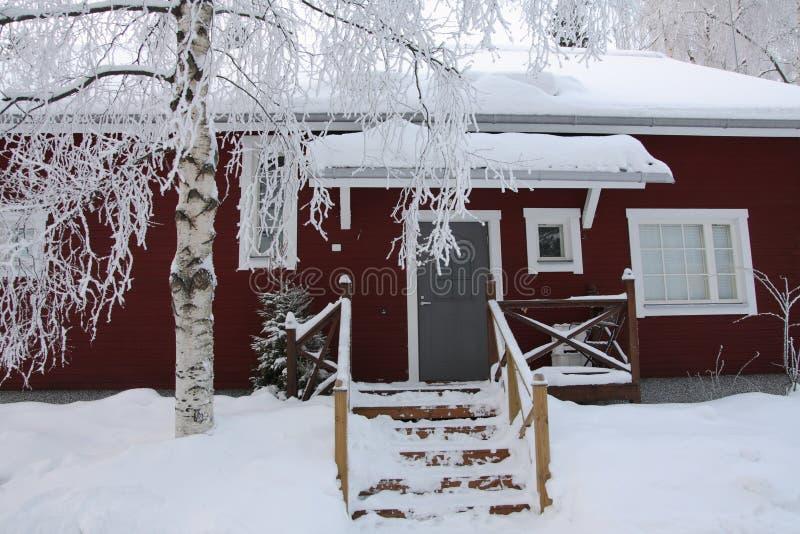 芬兰木房子红色的冬天 库存图片