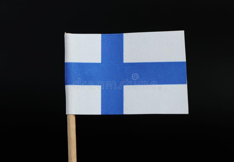 芬兰的一面正式旗子牙签的在黑背景 包括在白色领域的海蓝色北欧十字架 免版税库存图片