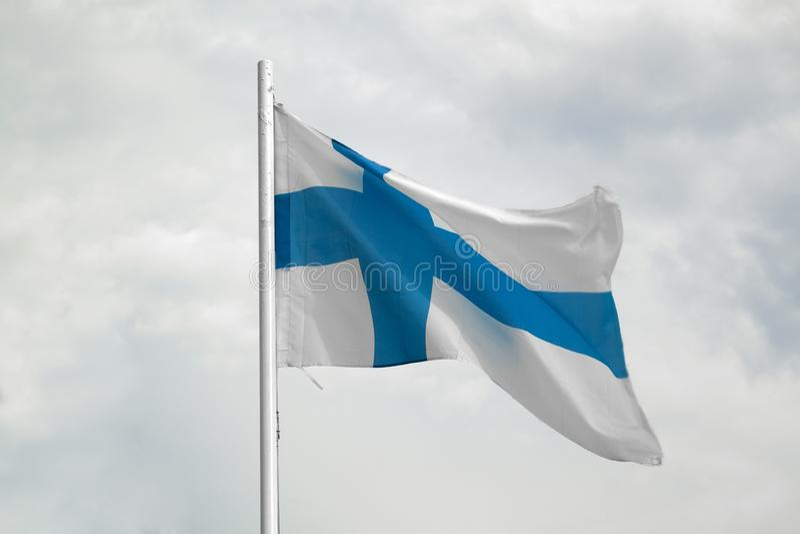 芬兰的旗子一天空蔚蓝的有云彩背景 库存图片
