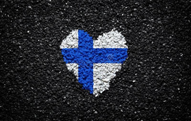 芬兰的旗子,芬兰旗子、心脏在黑背景,石头、石渣和木瓦,织地不很细墙纸 库存照片