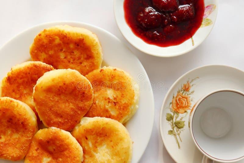 芬芳红润金黄与一个棕色外壳新近地烹调了糖浆curdscheesecake用的草莓酱和滚烫的酸性稀奶油 免版税图库摄影