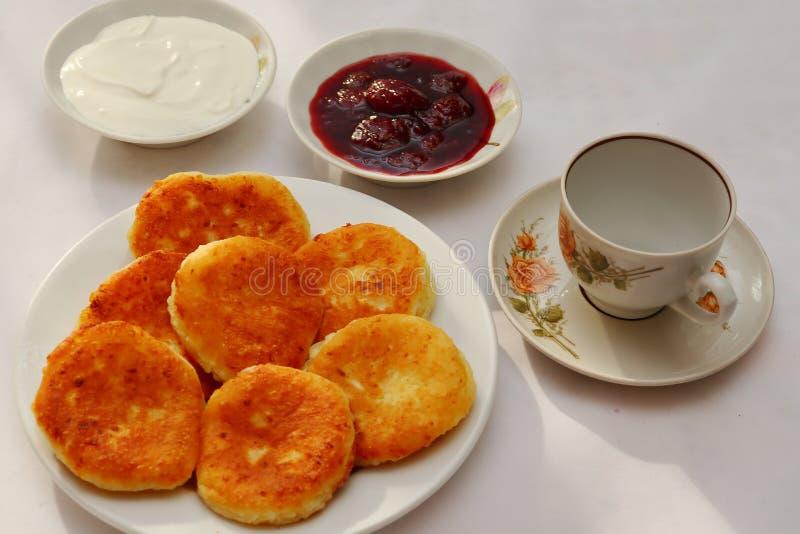 芬芳红润金黄与一个棕色外壳新近地烹调了糖浆curdscheesecake用的草莓酱和滚烫的酸性稀奶油 库存图片