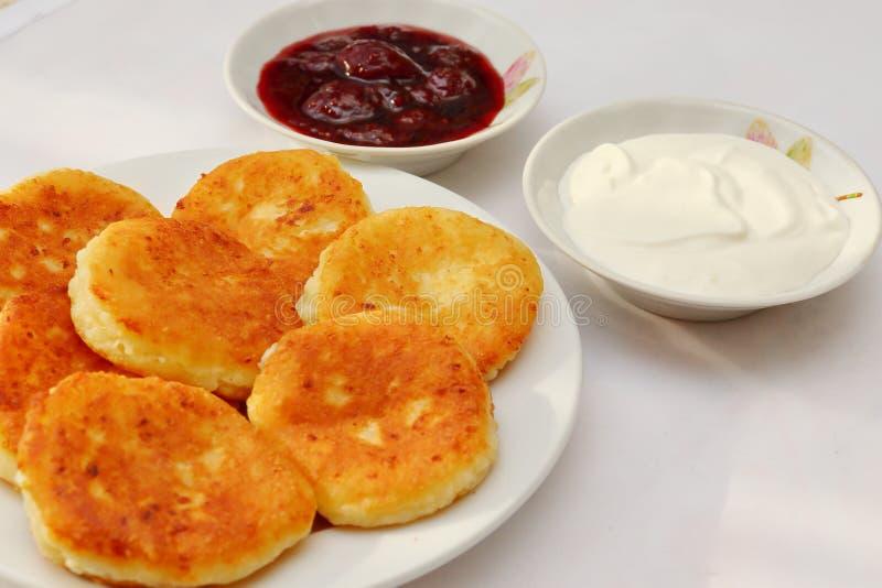 芬芳红润金黄与一个棕色外壳新近地烹调了糖浆curdscheesecake用的草莓酱和滚烫的酸性稀奶油 图库摄影