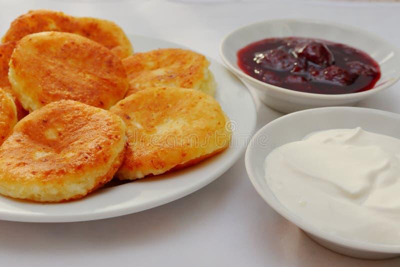 芬芳红润金黄与一个棕色外壳新近地烹调了糖浆curdscheesecake用的草莓酱和滚烫的酸性稀奶油 库存照片