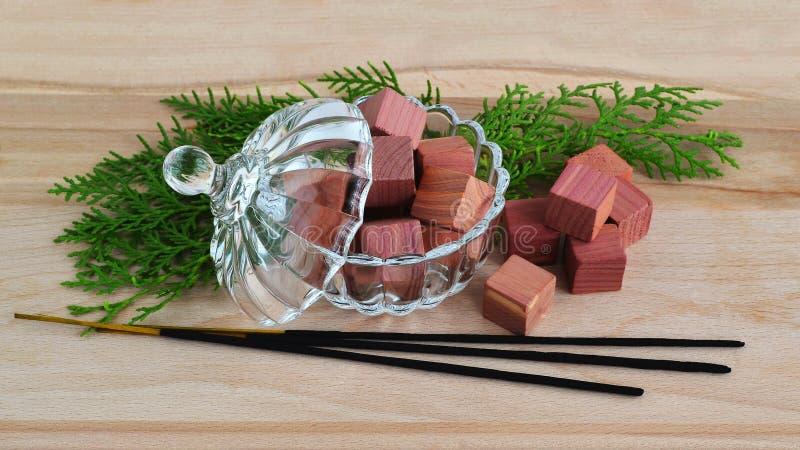 芬芳衣橱清凉剂立方体由在一个水晶碗的自然铅笔柏木头制成有盒盖,少量绿色柏小树枝和少量的 免版税库存照片
