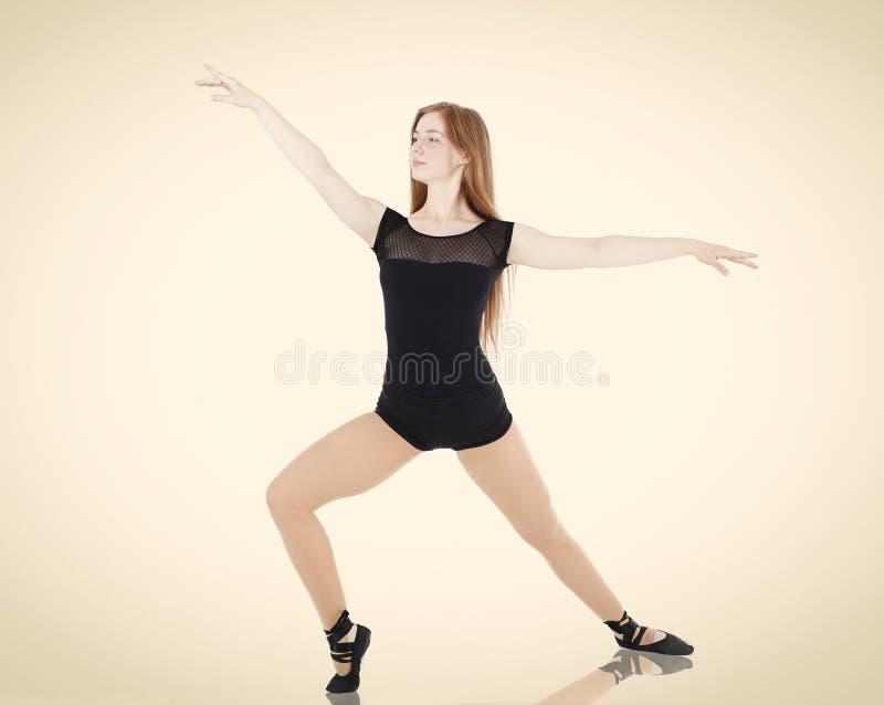 芭蕾姿势微笑的少妇舞蹈家 免版税图库摄影