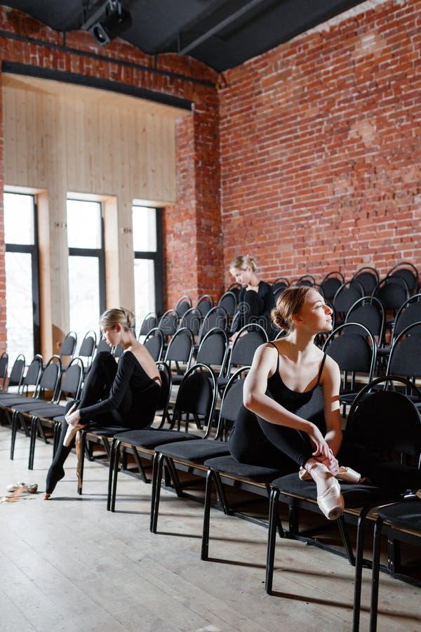 芭蕾概念 年轻芭蕾舞女演员女孩坐黑色椅子在大厅里 排练的妇女在黑色 免版税库存照片