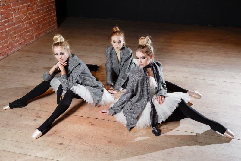 芭蕾概念 年轻芭蕾舞女演员女孩放松坐地板 排练的妇女在一件白色芭蕾舞短裙和灰色 免版税库存照片