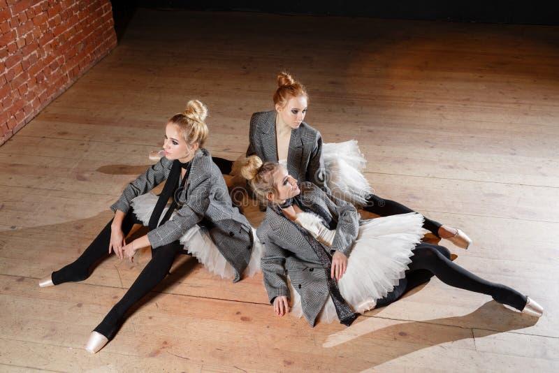 芭蕾概念 年轻芭蕾舞女演员女孩放松坐地板 排练的妇女在一件白色芭蕾舞短裙和灰色 图库摄影