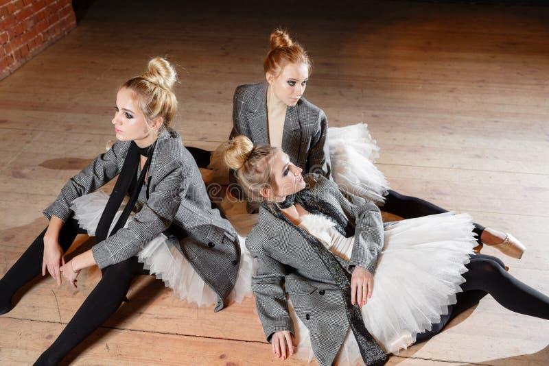 芭蕾概念 年轻芭蕾舞女演员女孩放松坐地板 排练的妇女在一件白色芭蕾舞短裙和灰色 库存图片