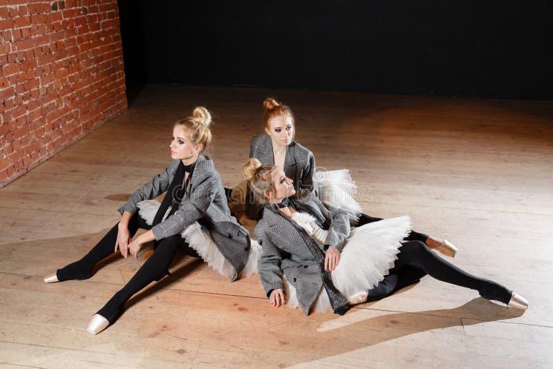 芭蕾概念 年轻芭蕾舞女演员女孩放松坐地板 排练的妇女在一件白色芭蕾舞短裙和灰色 库存照片
