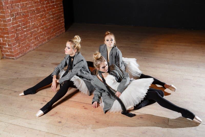 芭蕾概念 年轻芭蕾舞女演员女孩放松坐地板 排练的妇女在一件白色芭蕾舞短裙和灰色 免版税库存图片