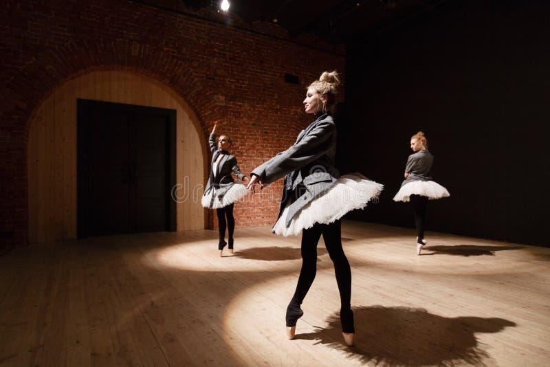 芭蕾概念 年轻芭蕾舞女演员女孩 排练的妇女在一件白色芭蕾舞短裙和一件灰色夹克 准备a 免版税库存图片